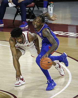 Kansas guard Marcus Garrett (0) is fouled by Oklahoma guard Elijah Harkless (24) during the second half of an NCAA college basketball game in Norman, Okla., Saturday, Jan. 23, 2021. (AP Photo/Garett Fisbeck)