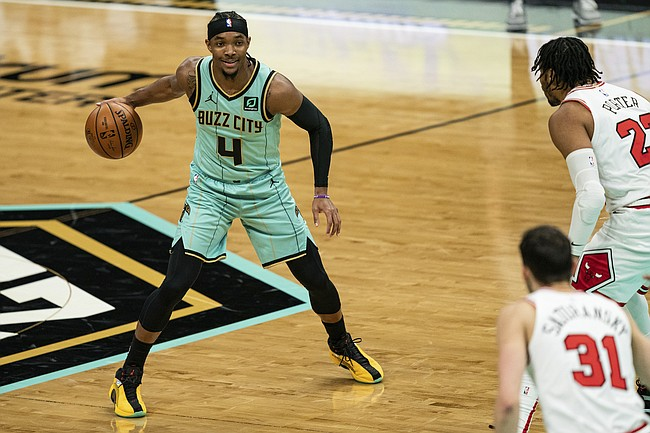 Charlotte Hornets guard Devonte' Graham (4) sets a play while guarded by Chicago Bulls forward Otto Porter Jr. (22) and guard Tomas Satoransky (31) during the first half of an NBA basketball game in Charlotte, N.C., Friday, Jan. 22, 2021. (AP Photo/Jacob Kupferman)