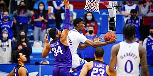 Kansas guard Tyon Grant-Foster (1) floats under TCU forward Kevin Easley (34) for a reverse layup during the second half on Thursday, Jan. 28, 2021 at Allen Fieldhouse.