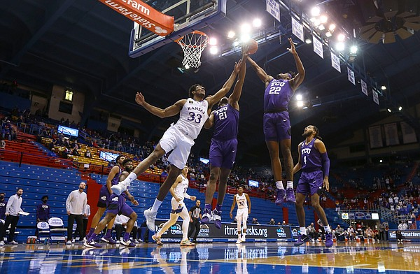 Kansas forward David McCormack (33) fights for a rebound with TCU guard RJ Nembhard (22) and TCU center Kevin Samuel (21) during the second half on Thursday, Jan. 28, 2021 at Allen Fieldhouse.