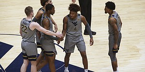 West Virginia players meet on the court during the second half of an NCAA college basketball game against Kansas, Saturday, Feb. 6, 2021, in Morgantown, W.Va. (AP Photo/Kathleen Batten)