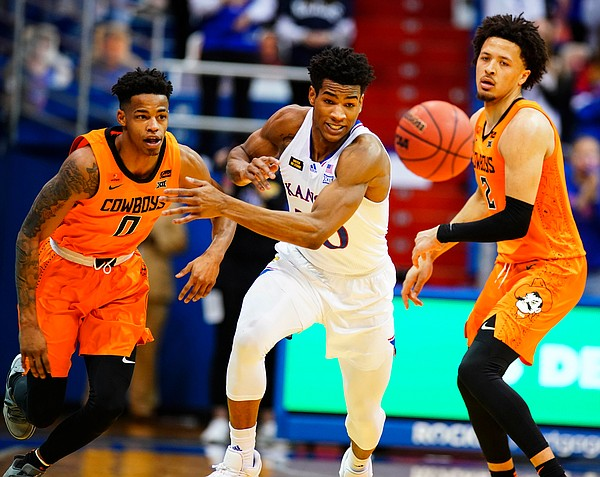 Kansas guard Ochai Agbaji and Oklahoma State guard Avery Anderson III (0) compete for a loose ball during the second half on Monday, Feb. 8, 2021 at Allen Fieldhouse.
