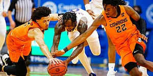 Kansas guard Marcus Garrett (0) competes for a ball with Oklahoma State forward Kalib Boone (22) after stripping it from Oklahoma State guard Cade Cunningham, left, during the second half on Monday, Feb. 8, 2021 at Allen Fieldhouse.