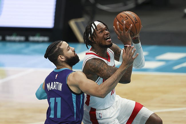 Houston Rockets guard Ben McLemore, right, drives to the basket against Charlotte Hornets forward Cody Martin (11) in the first half of an NBA basketball game in Charlotte, N.C., Monday, Feb. 8, 2021. (AP Photo/Nell Redmond)