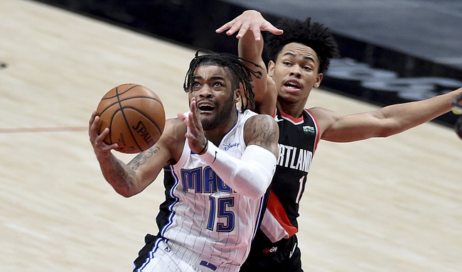 Orlando Magic guard Frank Mason III, left, drives to the basket on Portland Trail Blazers guard Anfernee Simons, right, during the first half of an NBA basketball game in Portland, Ore., Tuesday, Feb. 9, 2021. (AP Photo/Steve Dykes)