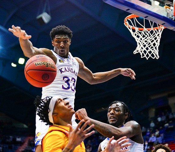 Kansas forward David McCormack (33) comes over the top of a shot by Iowa State guard Jaden Walker (21) during the first half on Thursday, Feb. 11, 2021 at Allen Fieldhouse. At right is Kansas guard Marcus Garrett (0).