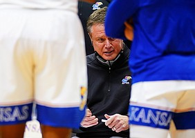 Kansas head coach Bill Self huddles up with his players during the second half on Thursday, Feb. 11, 2021 at Allen Fieldhouse.
