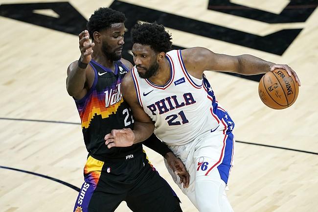 Philadelphia 76ers center Joel Embiid (21) drives on Phoenix Suns center Deandre Ayton during the first half of an NBA basketball game, Saturday, Feb. 13, 2021, in Phoenix.(AP Photo/Matt York)
