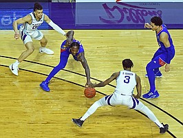KU senior Marcus Garrett attempts to make a move through defenders during a game against K-State at Bramlage Coliseum in Manhattan, Kansas on February 17, 2021.