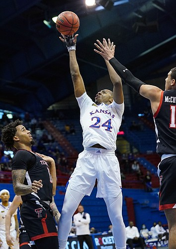 Kansas guard Bryce Thompson (24) shoots against Texas Tech Red Raiders guard Kyler Edwards (11) and guard Kevin McCullar (15) during the first half at Allen Fieldhouse Saturday afternoon in Allen Fieldhouse on Feb. 20, 2021. Photo by Jay Biggerstaff-USA TODAY Sports.