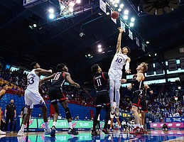 Kansas forward Jalen Wilson (10) shoots against Texas Tech guard Kyler Edwards (11) and guard Mac McClung (0) during the first half at Allen Fieldhouse Saturday afternoon in Allen Fieldhouse on Feb. 20, 2021. Photo by Jay Biggerstaff-USA TODAY Sports.