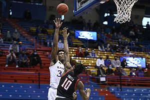 Kansas big man David McCormack shoots over a Texas Tech defender during a game against Texas Tech Saturday afternoon in Allen Fieldhouse on Feb. 20, 2021. Photo by Mike Gunnoe.