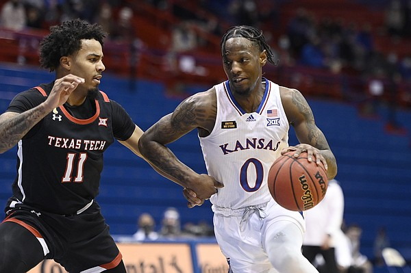 Kansas senior Marcus Garrett attempts to drive past a Texas Tech defender during a game against Texas Tech Saturday afternoon in Allen Fieldhouse on Feb. 20, 2021. Photo by Mike Gunnoe.