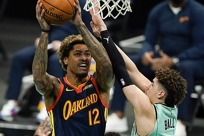 Golden State Warriors guard Kelly Oubre Jr. (12) shoots over Charlotte Hornets guard LaMelo Ball during the first half of an NBA basketball game on Saturday, Feb. 20, 2021, in Charlotte, N.C. (AP Photo/Chris Carlson)