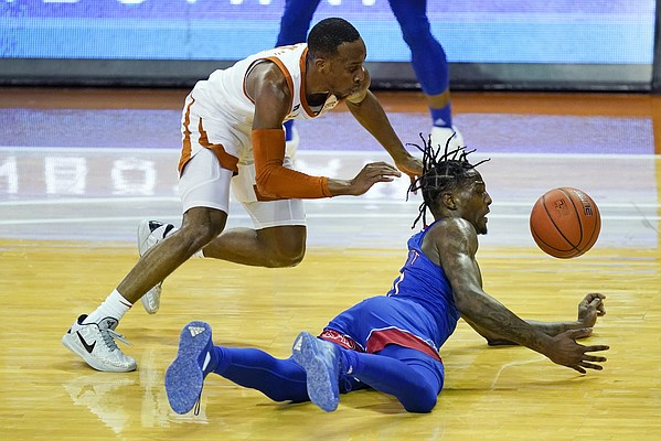 Texas guard Matt Coleman III, left, fights for a loose ball with Kansas guard Marcus Garrett during the second half of an NCAA college basketball game, Tuesday, Feb. 23, 2021, in Austin, Texas. (AP Photo/Eric Gay)