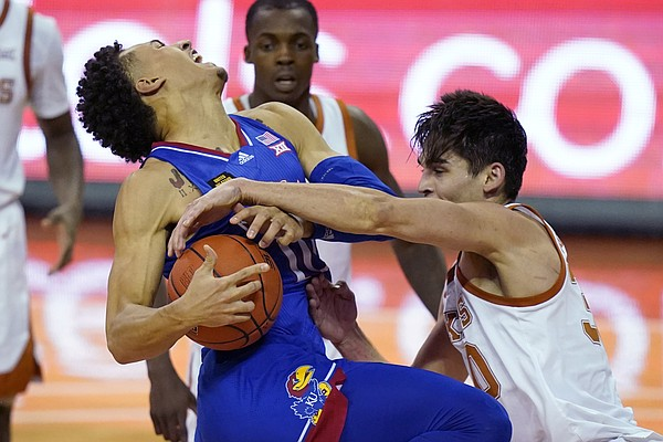Kansas forward Jalen Wilson is fouled by Texas forward Brock Cunningham, right, while driving to the basket during the second half of an NCAA college basketball game, Tuesday, Feb. 23, 2021, in Austin, Texas. (AP Photo/Eric Gay)