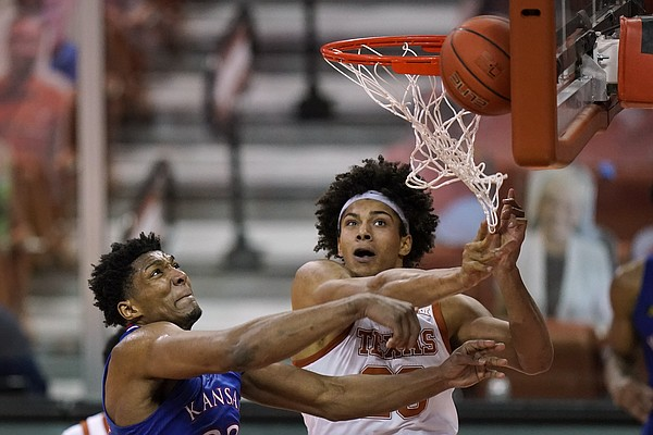Kansas forward David McCormack, left, fights for a rebound with Texas forward Jericho Sims during the second half of an NCAA college basketball game, Tuesday, Feb. 23, 2021, in Austin, Texas. (AP Photo/Eric Gay)