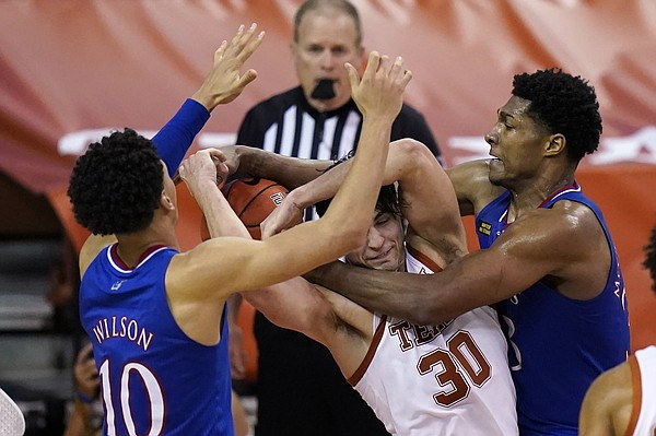 Texas forward Brock Cunningham, center, fights for a rebound with Kansas forward Jalen Wilson, left, and forward David McCormack, right, during overtime in an NCAA college basketball game, Tuesday, Feb. 23, 2021, in Austin, Texas. (AP Photo/Eric Gay)