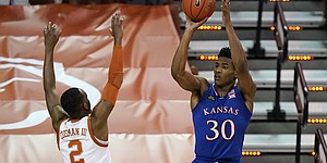 Kansas guard Ochai Agbaji (30) shoots over Texas guard Matt Coleman III (2) during the first half of an NCAA college basketball game, Tuesday, Feb. 23, 2021, in Austin, Texas. (AP Photo/Eric Gay)