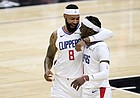 Los Angeles Clippers forward Marcus Morris Sr., left, hugs guard Reggie Jackson in the closing seconds of an NBA basketball game against the Washington Wizards on Tuesday, Feb. 23, 2021, in Los Angeles. The Clippers won 135-116. (AP Photo/Mark J. Terrill)