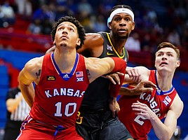 Kansas forward Jalen Wilson (10) and Kansas guard Christian Braun (2) box out Baylor forward Flo Thamba (0) during the second half on Saturday, Feb. 27, 2021 at Allen Fieldhouse.