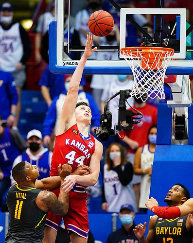 Kansas forward Mitch Lightfoot (44) gets up for a bucket over Baylor guard Mark Vital (11) during the second half on Saturday, Feb. 27, 2021 at Allen Fieldhouse. At right is Baylor guard Jared Butler (12).