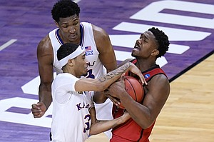 Kansas guard Dajuan Harris (3) battles Eastern Washington guard Kim Aiken Jr. (24) battle for the ball during the second half of a first-round game in the NCAA college basketball tournament at Farmers Coliseum in Indianapolis, Saturday, March 20, 2021. (AP Photo/AJ Mast)
