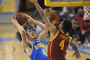 UCLA guard Jaime Jaquez Jr., left, shoots as Southern California forward Evan Mobley defends during the second half of an NCAA college basketball game Saturday, March 6, 2021, in Los Angeles. USC won 64-63. (AP Photo/Mark J. Terrill)