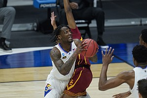 Kansas guard Marcus Garrett (0) tries to shoot around a USC defender during the first half of a men's college basketball game in the second round of the NCAA tournament at Hinkle Fieldhouse in Indianapolis, Monday, March 22, 2021. (AP Photo/Paul Sancya)
