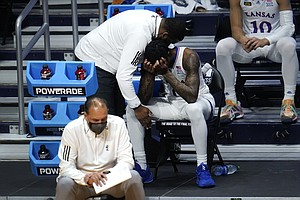 Kansas guard Marcus Garrett (0) is comforted by staff during the second half of a men's college basketball game in the second round of the NCAA tournament at Hinkle Fieldhouse in Indianapolis, Monday, March 22, 2021. USC won 85-51. (AP Photo/Paul Sancya)