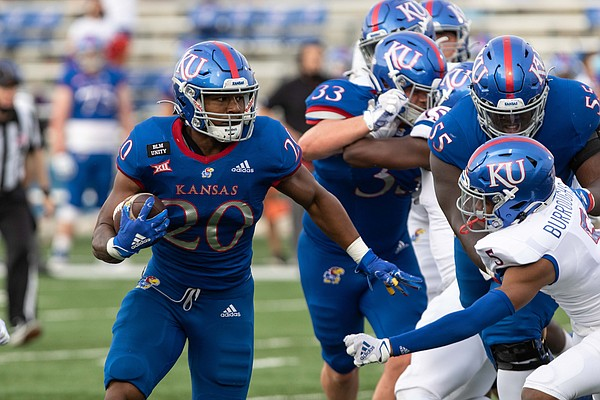 Sophomore running back Daniel Hishaw Jr. attempts to get by the defense during the Kansas Football Spring Game. The White team defeated the Blue team 74-42 Saturday, May 1, 2021.
