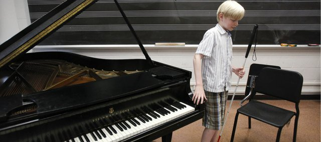 Twelve-year-old Luther Fuller, a pianist who is blind, navigates his way around a grand piano that he will soon practice on during a tour of Murphy Hall, Monday, July 2, 2012. Fuller spent part of the day with his mother, Brendy Latare, learning the lay of the building in preparation for the upcoming International Institute for Young Musicians Summer Music Academy, which begins on July 8. Nick Krug/Journal-World Photo